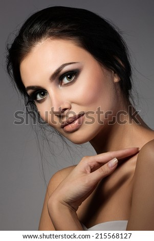 Portrait of young beautiful brunette woman looking straight to camera - stock photo
