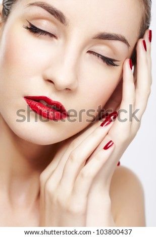 portrait of young beautiful brunette woman on gray with eyes shut - stock photo