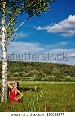 Portrait of young beautiful brunette woman red bright dress, standing on grass at summer - stock photo