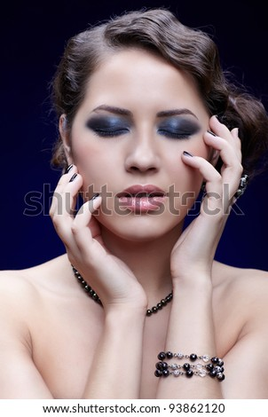 portrait of young beautiful brunette woman with eyes shut posing in beads and bracelet - stock photo