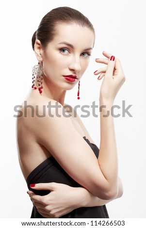 portrait of young beautiful brunette woman with manicured hands in ear-rings on gray - stock photo