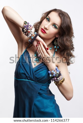 portrait of young beautiful brunette woman with manicured hands posing in blue dress and jewelry on gray - stock photo