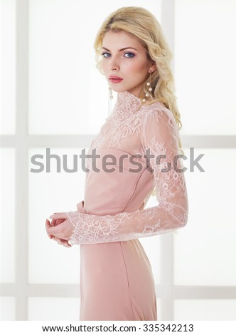 Portrait of young beautiful caucasian blonde girl in gorgeous dress on white background - stock photo