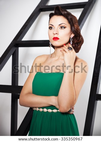 Portrait of young beautiful caucasian brunette woman in gorgeous green dress with hairdress on white background - stock photo