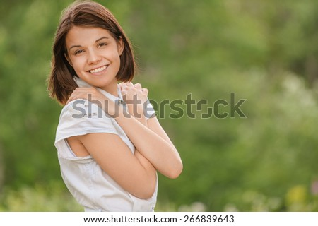 Portrait of young beautiful cheerful woman wearing white clothes at summer green park. - stock photo