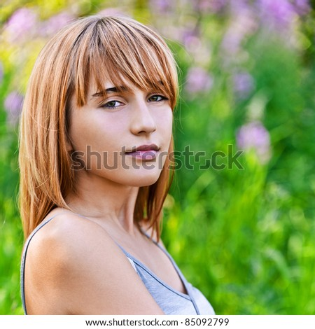 Portrait of young beautiful content blond woman at summer green park. - stock photo
