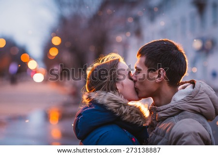 Portrait of young beautiful couple kissing in an autumn rainy day. Love  and couple relationships concept. - stock photo