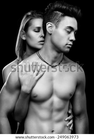 portrait of young beautiful couple on black - stock photo