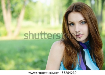 Portrait of young beautiful dark-haired woman at summer green park. - stock photo