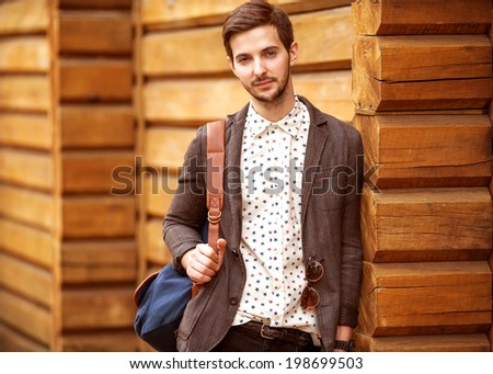 Portrait of young beautiful fashionable man against wooden wall. Hipster style guy - stock photo