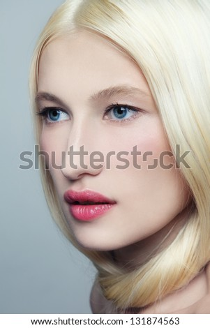 Portrait of young beautiful fresh woman with long bleached hair and clear make-up looking upwards - stock photo