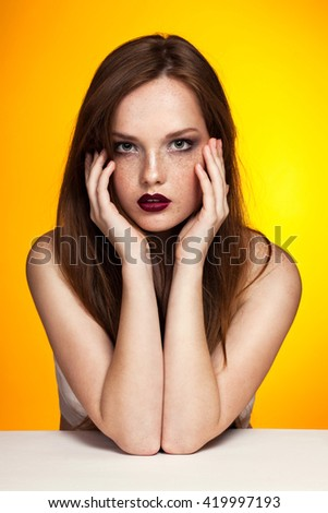 Portrait of young beautiful ginger girl with red lips on a bright yellow background. Sensual bright lips, white skin, passionate look, freckles, long hair. Fashion woman, Vogue. - stock photo