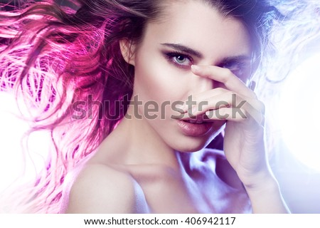 Portrait of young beautiful girl  brunette, amid spotlight. The effect  toning, night club, dance culture - stock photo