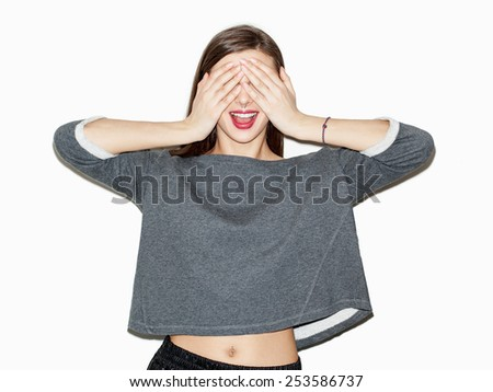 Portrait of young beautiful girl covering her face with hands. Bright makeup and red lips. White background, not isolated. Inside. - stock photo