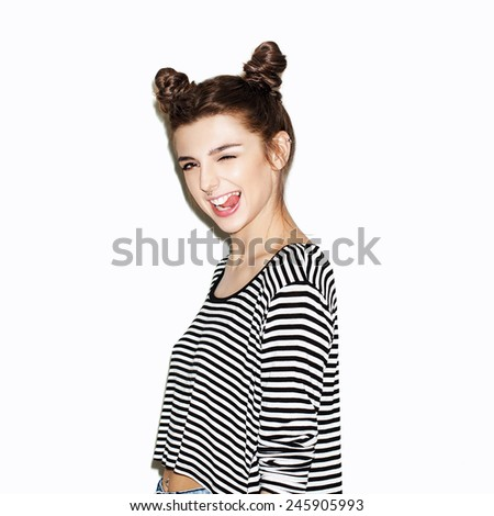 Portrait of young beautiful girl having fun and showing tongue. Bright makeup and top knot hairdo. White background, not isolated. Inside. - stock photo