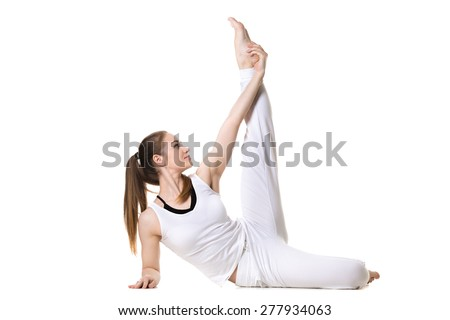 Portrait of young beautiful girl in white sportswear doing yoga or pilates practice, stretching exercises for legs, side view, studio shot, isolated - stock photo