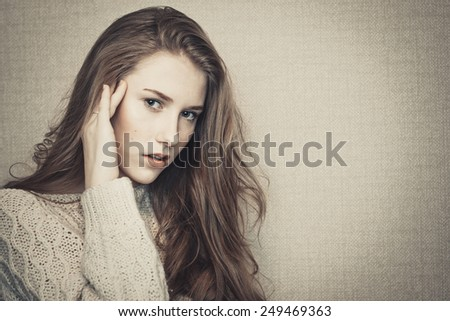 Portrait of young beautiful girl looking at camera with hand on her cheek  - stock photo