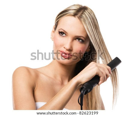 Portrait of young beautiful girl making hairstyle with hair iron - stock photo