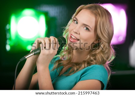 Portrait of young beautiful girl singing. closeup of blond girl holding mic and tilting head - stock photo