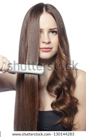 Portrait of young beautiful girl using styler on her shining hair - stock photo