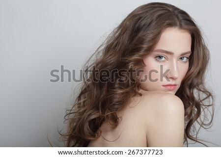 Portrait of young beautiful girl with clear skin and long healthy curly hair - stock photo