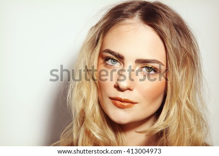 Portrait of young beautiful girl with long messy hair and golden make-up - stock photo