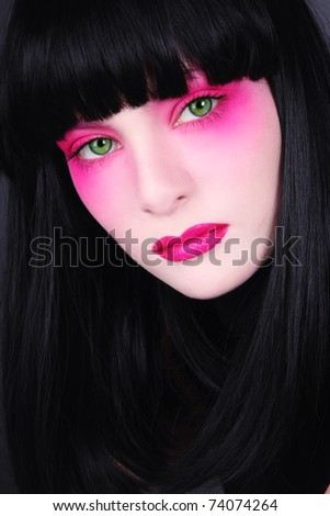 Portrait of young beautiful green-eyed brunette with fancy pink make-up - stock photo