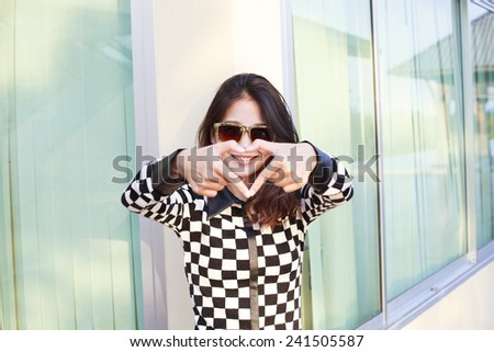 portrait of young beautiful hipster woman wearing sun glasses making heart symbol by finger hand - stock photo