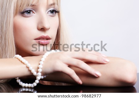 portrait of young beautiful long-haired blonde woman with pearl beads - stock photo