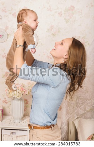 Portrait of young beautiful mother lifting baby boy at the bedroom. Pretty woman throwing up cheerful little child on light room background, happy healthy family, love concept - stock photo
