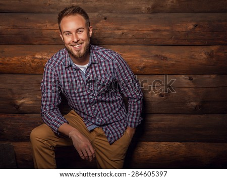 Portrait of young beautiful positive man against old wooden wall.  - stock photo