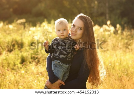 Portrait of young beautiful pretty mother holding son on hands and posing in field with high grass at sunset on a sunny evening. Warm colors photo - stock photo