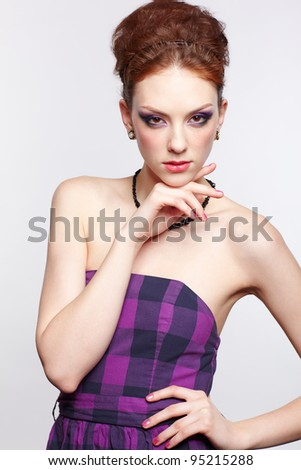 portrait of young beautiful red-haired woman in violet dress with one hand under chin - stock photo