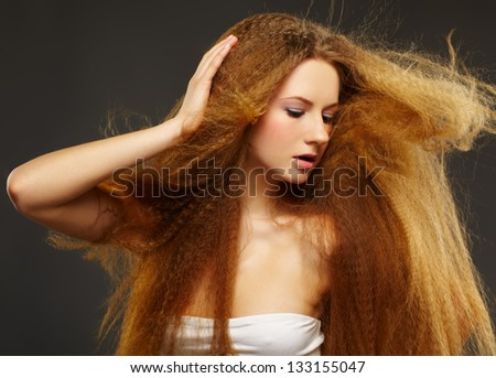 portrait of young beautiful red-haired woman with waving hair posing on gray - stock photo