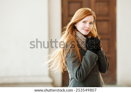 Portrait of young beautiful redhead lady wearing coat and scarf posing outdoors with architectural background - stock photo
