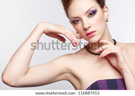 portrait of young beautiful redhead woman in violet dress touching her face with hands - stock photo