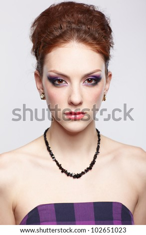 portrait of young beautiful redhead woman on gray - stock photo