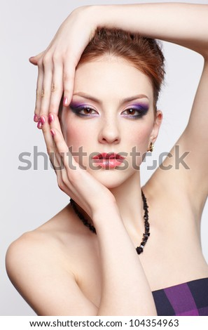 portrait of young beautiful redhead woman with purple eye shadow touching her face with hands - stock photo