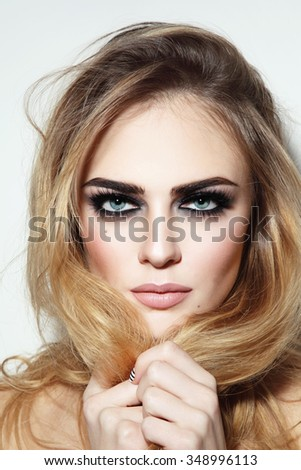 Portrait of young beautiful sexy blond girl with smoky eyes and long damaged hair - stock photo