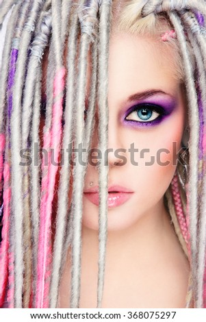 Portrait of young beautiful sexy girl with stylish bright make-up and dreadlocks - stock photo