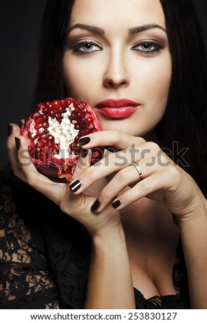 Portrait of young beautiful sexy woman with juicy pomegranate in her hand - stock photo