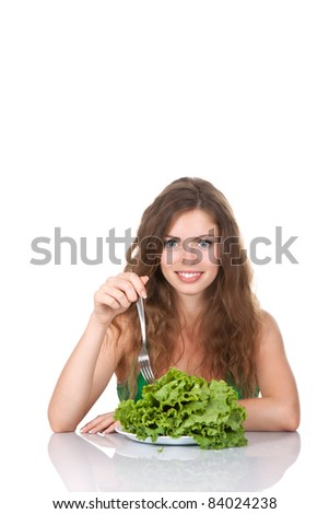portrait of young beautiful smile woman sitting at the table eat green fresh raw salad leaf on dish, isolated on white background - stock photo
