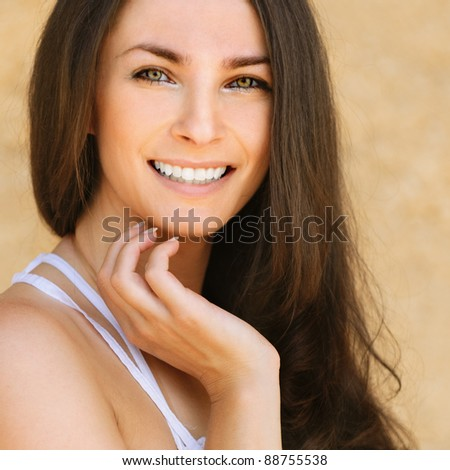 Portrait of young beautiful smiling brunette woman wearing white dress against yellow background. - stock photo