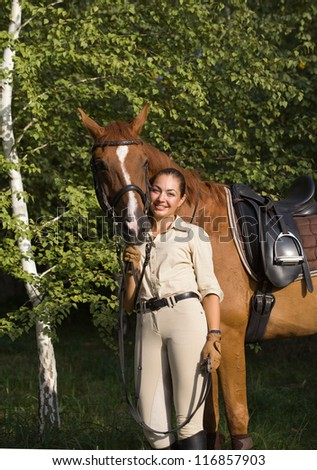 Portrait of young beautiful smiling brunette woman with a brown horse - stock photo