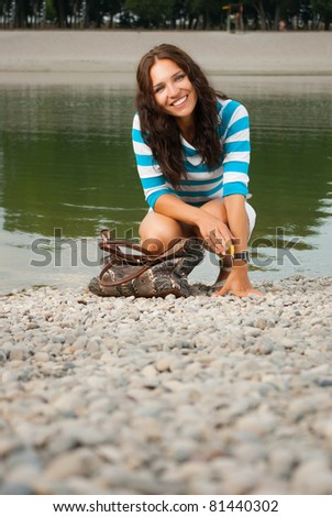 Portrait of young beautiful smiling female near the lake - stock photo