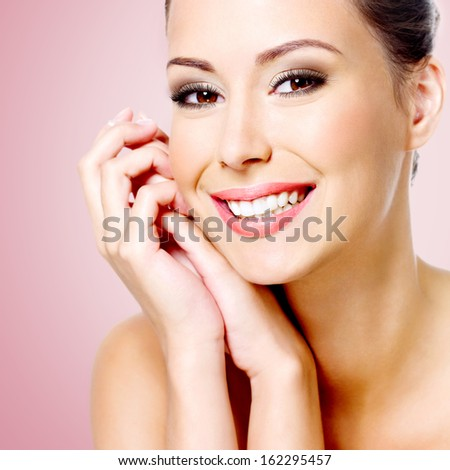 Portrait of young beautiful smiling white woman with healthy skin of face - stock photo