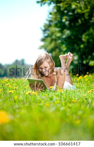 Portrait of young beautiful smiling woman with tablet pc, outdoors - stock photo
