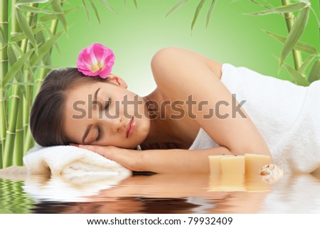 Portrait of young beautiful spa woman with flower in her hair lying and relaxing - stock photo