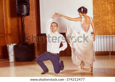 Portrait of young beautiful wedding couple dancing at restaurant background. - stock photo