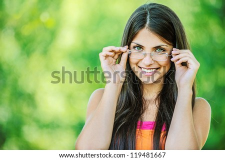 Portrait of young beautiful woman adjusts glasses and smiling, on green background summer nature. - stock photo